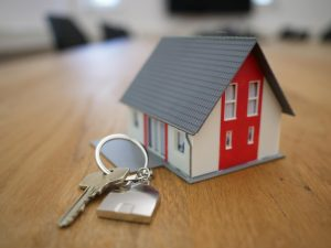 miniature house model with padlock and key